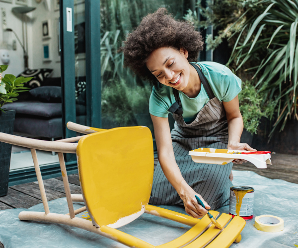Woman painting chair yellow